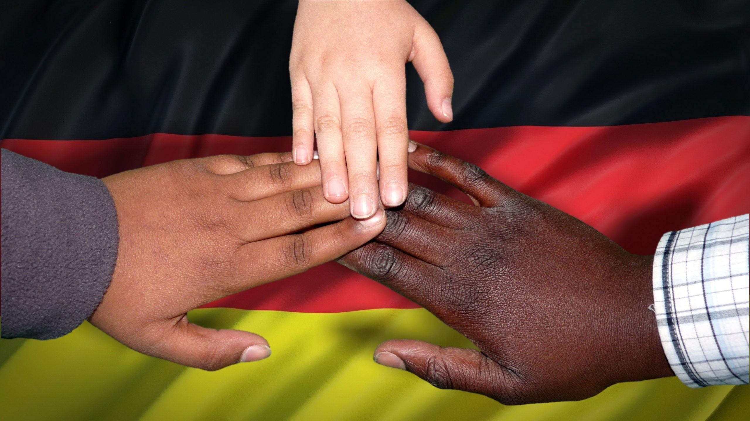 Integration - drei Hände unterschiedlicher Hautfarbe, im Hintergrund ist die deutsche Nationalflagge